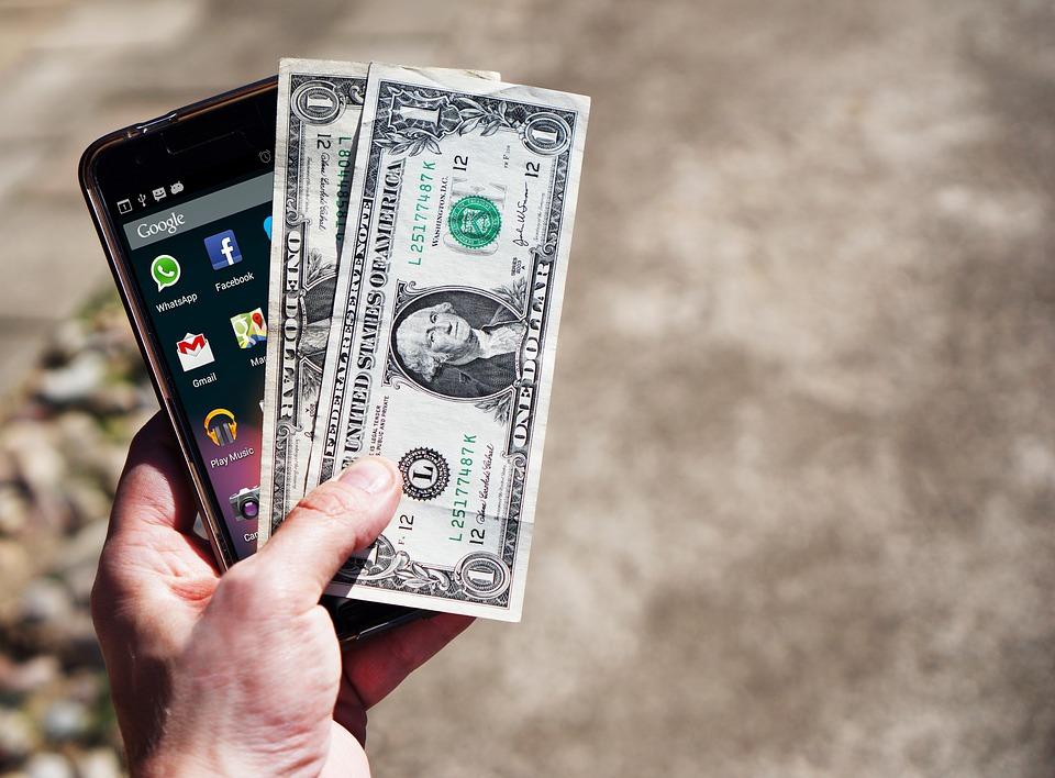 Hånd der holder pengesedler og mobil