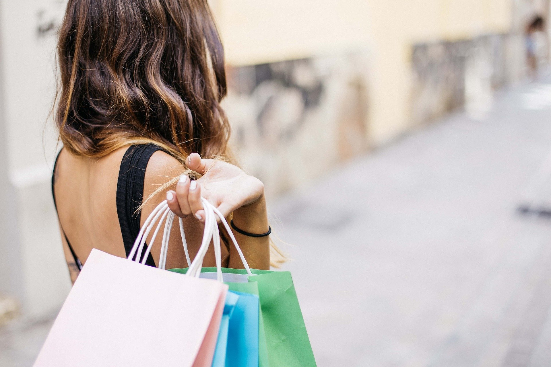 Ung kvinde med indkøbsposer over den ene skulder